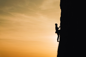 Person scaling cliff face