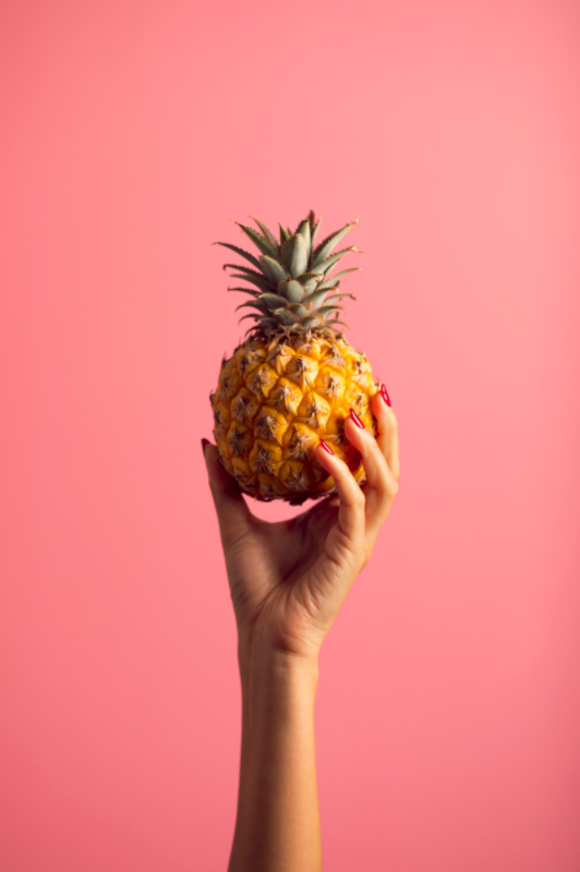 Pineapple in a hand, rose background