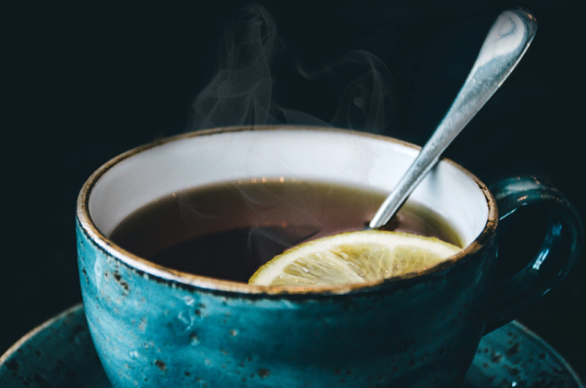 steaming tea in a blue ceramic cup with lemon and spoon