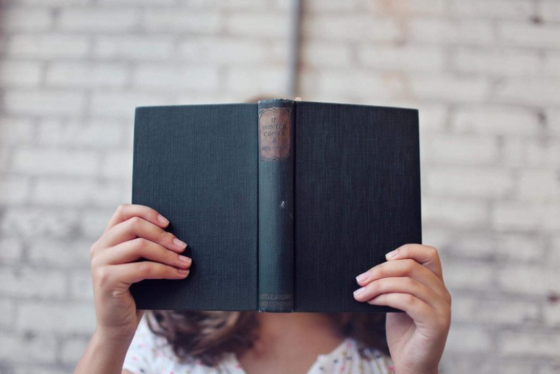woman reading book covering face