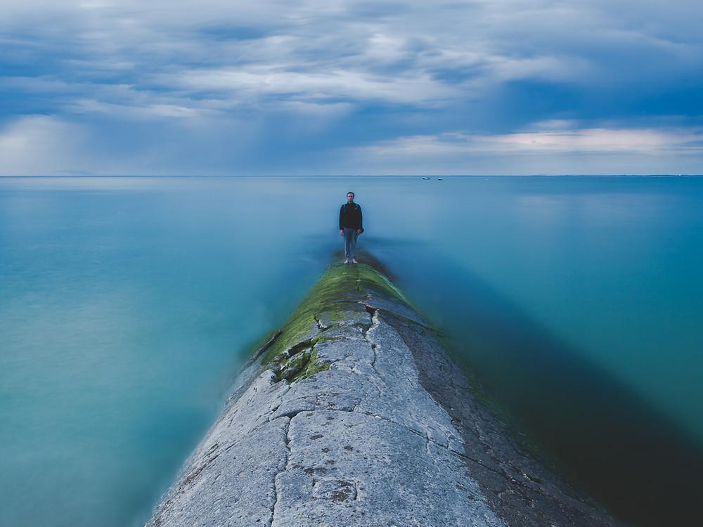 un homme qui marche au bord de l'océan
