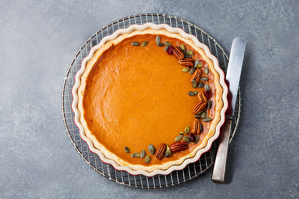Top-down shot of pumpkin pie with knife on table
