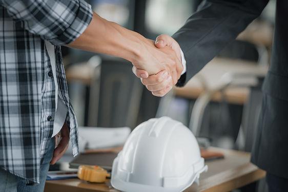 business-people-shaking-hands-together-desk.jpeg