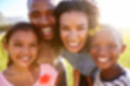 Laughing black family outdoors, close up