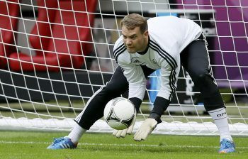 Germany's national soccer team goalkeeper Manuel Neuer dives for a ball during a practice session for the Euro 2012 at the stadium in Warsaw June 27, 2012. Germany will play a semi-final of the Euro 2012 soccer championships against Italy on Thursday June 28, 2012. REUTERS/Pascal Lauener (POLAND - Tags: SPORT SOCCER)