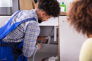Woman Looking At Male Plumber Cleaning C