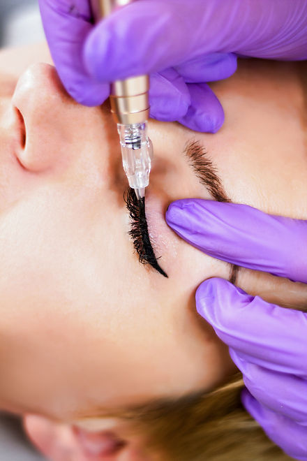 Woman having permanent makeup on eyeliner in beautician salon.jpg