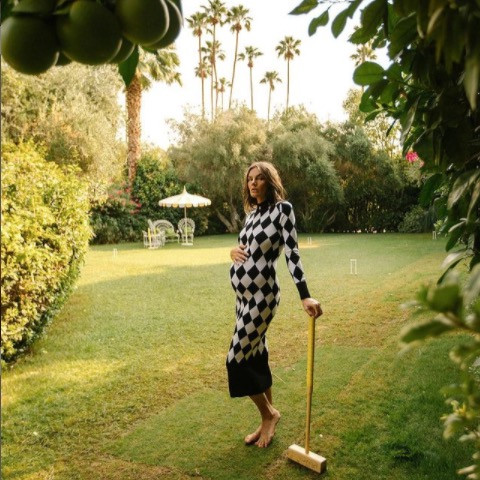 pregnant woman standing on lawn in checkerboard knit dress