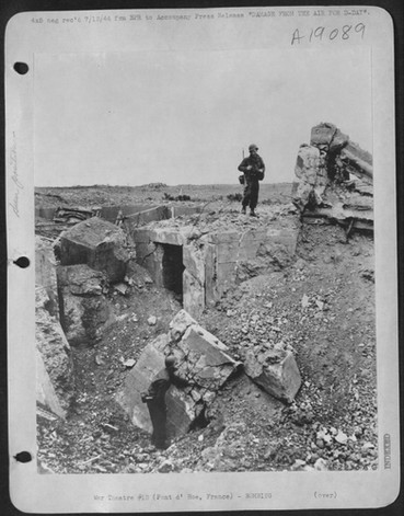 Soldier standing on top of destroyed bunker at Pointe du Hoc