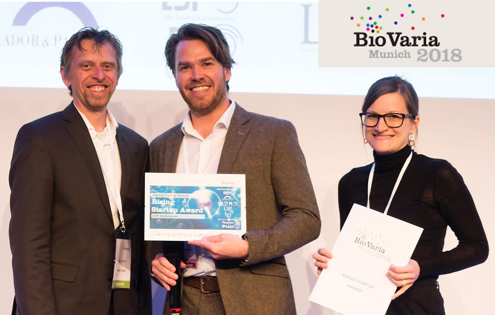 Alex Blyth, CEO to LIfT BioSciences collects the award from Dr Dirk Vocke of Merck KGaA and Dr Nadine Sobotzki of M-Ventures