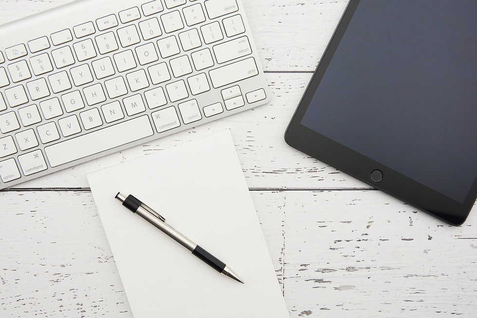 Tools of a virtual assistant - a desktop with keyboard, tablet, notebook and pen.