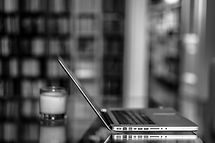 A laptop and a candle in a library, all very organised and calm.