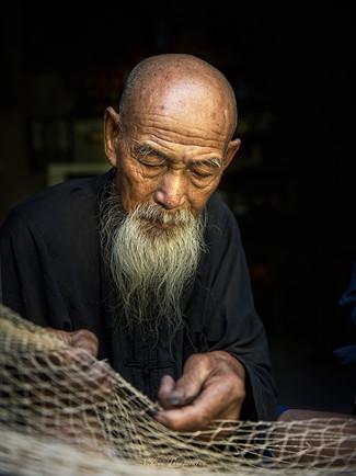 Cormorant elder fisherman mending net.jp