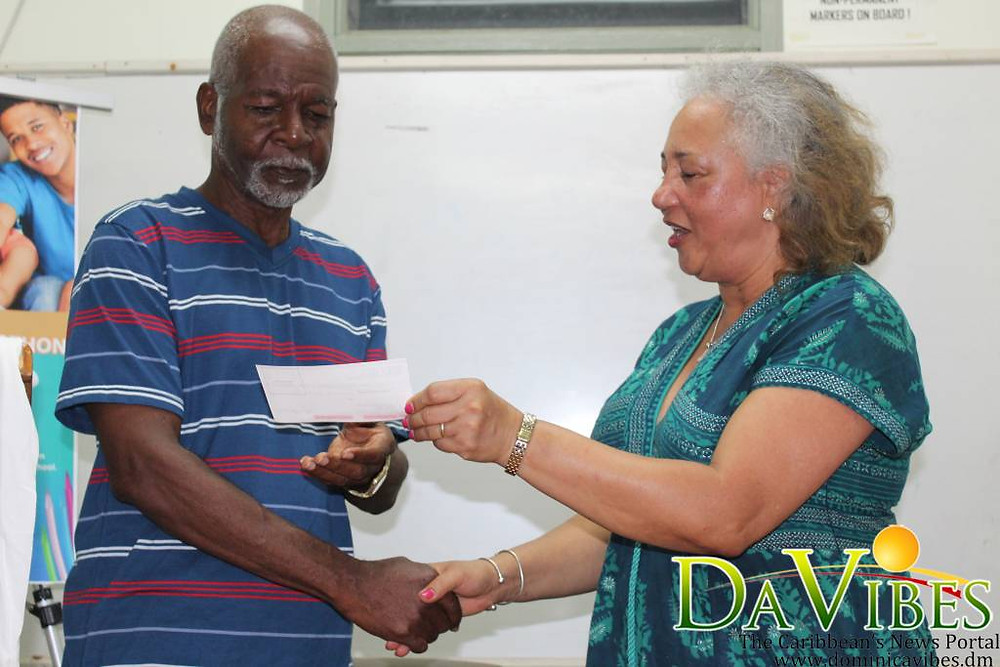 DASSSA representative, Cathy McClain presenting the cheque to Chairman of the Education Trust Fund, Willy Fevrier