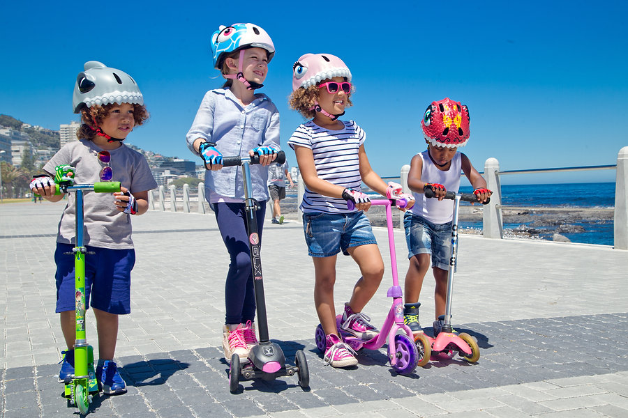 Kids on scooters with Cool Kiwi Kids helmets made by Crazy Safety!
