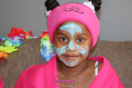 Little girl with face mask and pink spa gown at a Sugar Angel Pamper Party