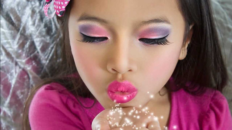 Litlle girl with pink & purple eye shadow blowing Angel Dust