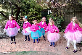 Pretty little girls dancing with pink tutus at a pamper party