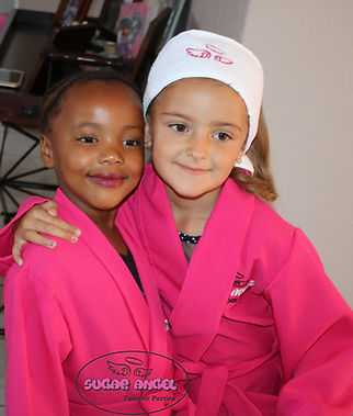 Friends with pink spa gowns hugging at Girls birthday party