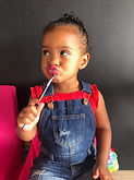 Little girl sitting and posing with a make-up brush