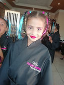Little girl smiling for the camera in her black spa gown outfit at her birthday pamper party