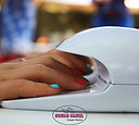 Little girl drying her newly painted nails in a Sugar Angel nail dryer