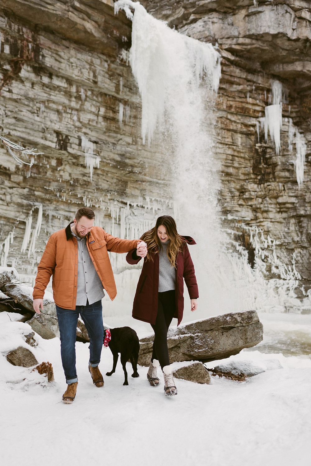 Couple walks with their dog in front of Awosting Falls in Minnewaska State Park in upstate NY
