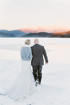 Couple stands in front of Whiteface Mountain at their winter wedding in the Lake Placid Lodge