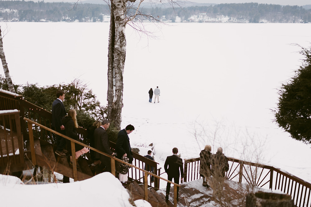 Wedding guests walk on frozen Schroon Lake in preparation for the wedding ceremony