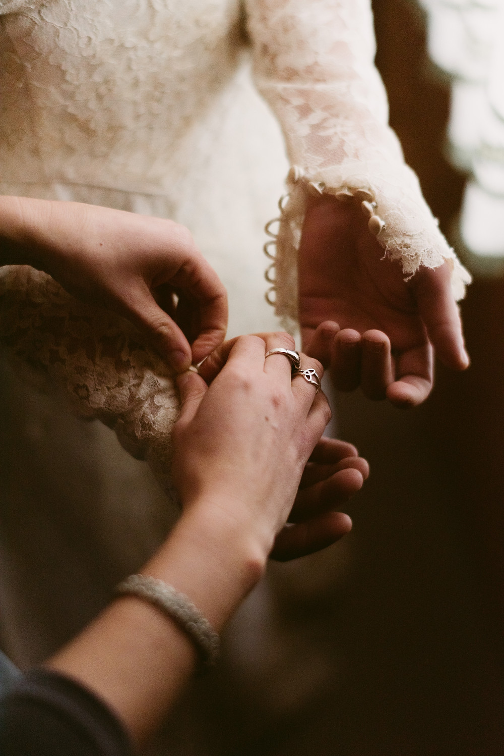 Bridesmaid buttons bride into her antique lace wedding gown
