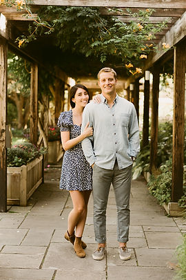 Couple poses in front of botanical gardens at Cornell University