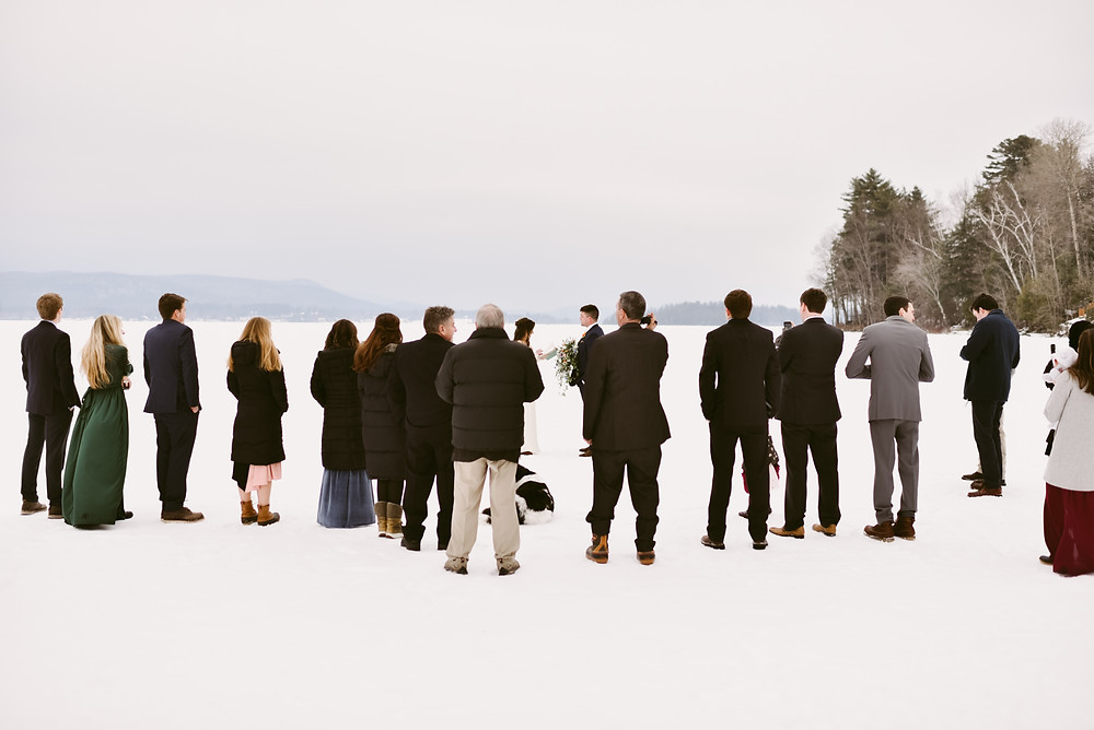 Family members gather around couple as they get married on a frozen lake