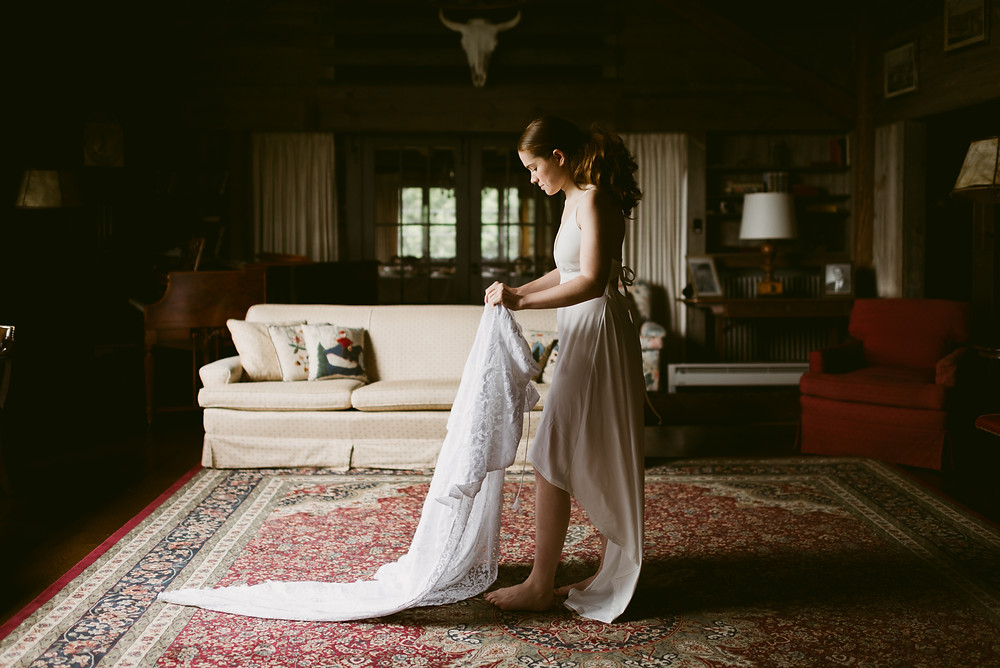 Bride prepares to step into her wedding gown at The River Ranch in upstate New York