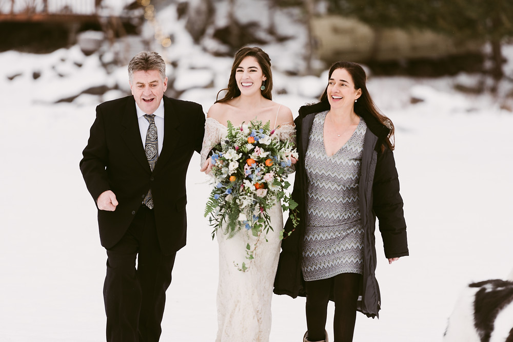 Bride and parents smile as they approach the groom