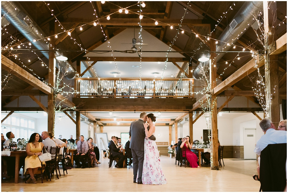 Romantic first dance in a barn with string lights