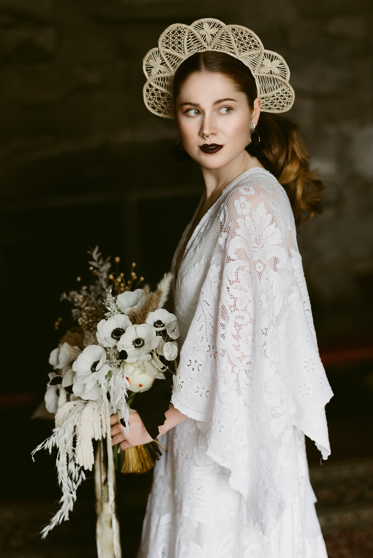 Window-lit portrait of an alternative bride on her Lake Placid wedding day