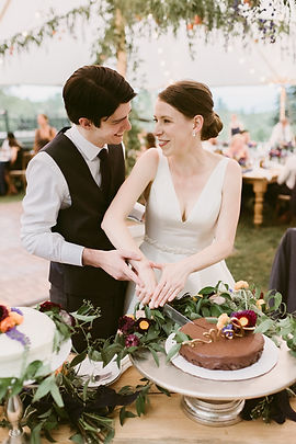 Couple smiles at one another before cutting their wedding cake
