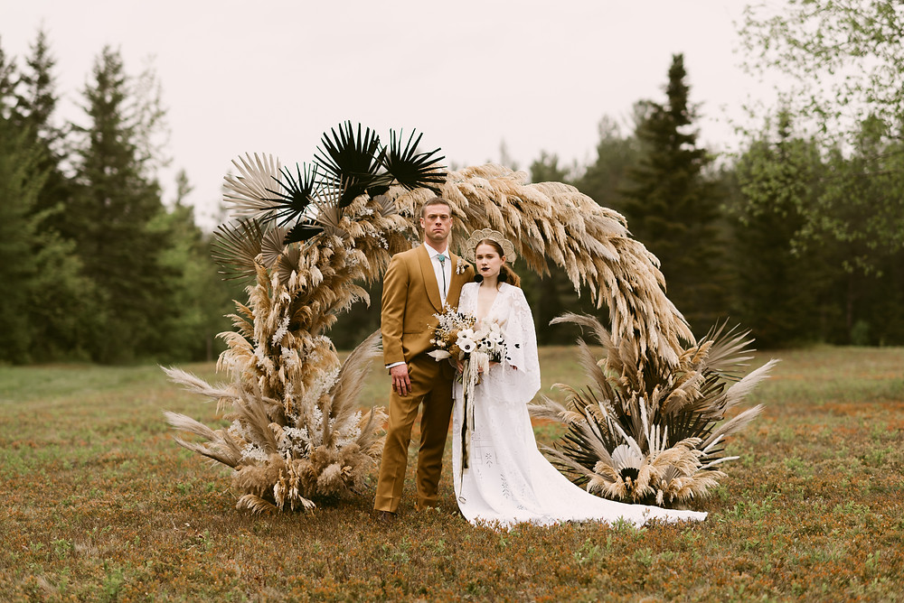 Alternative wedding couple standing in front of a pampas grass arch at the River Ranch in Lake Placid, NY