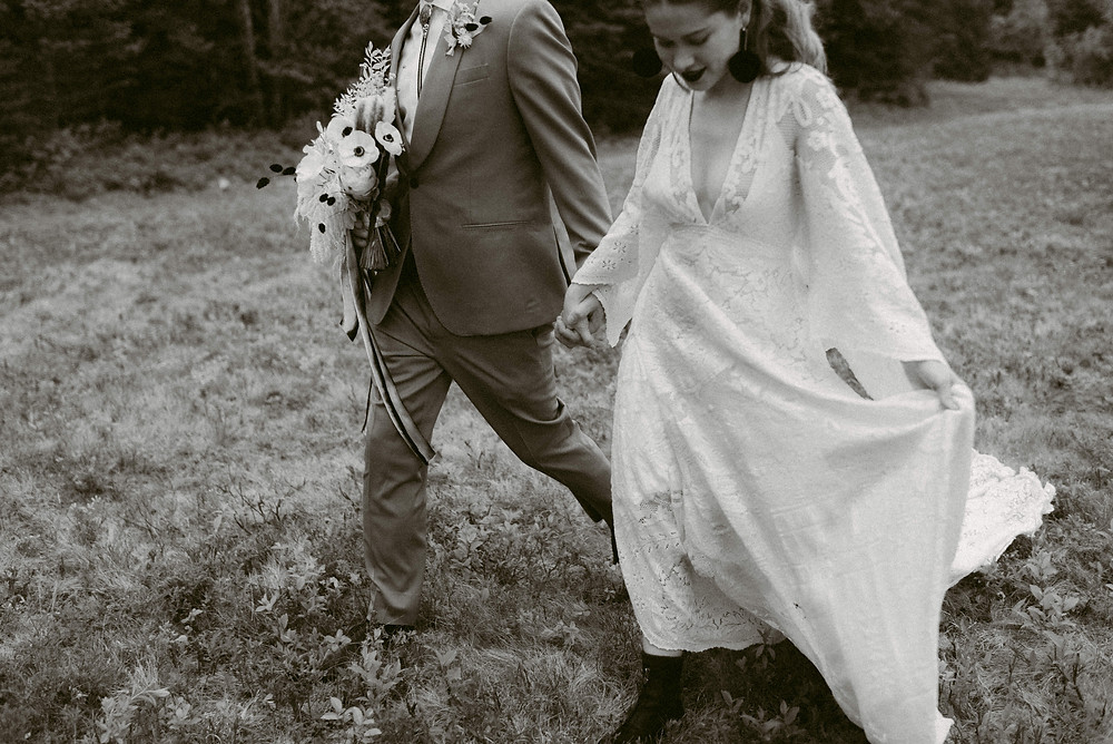 Black and white image of bride and groom walking hand in hand after their Adirondack wedding ceremony