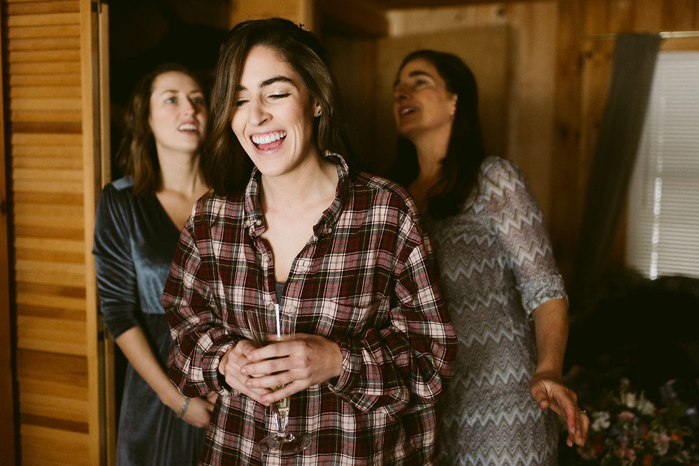 Bride, wearing plaid, laughs on her wedding day