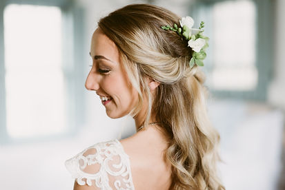Summer bride smiles with flowers in her hair
