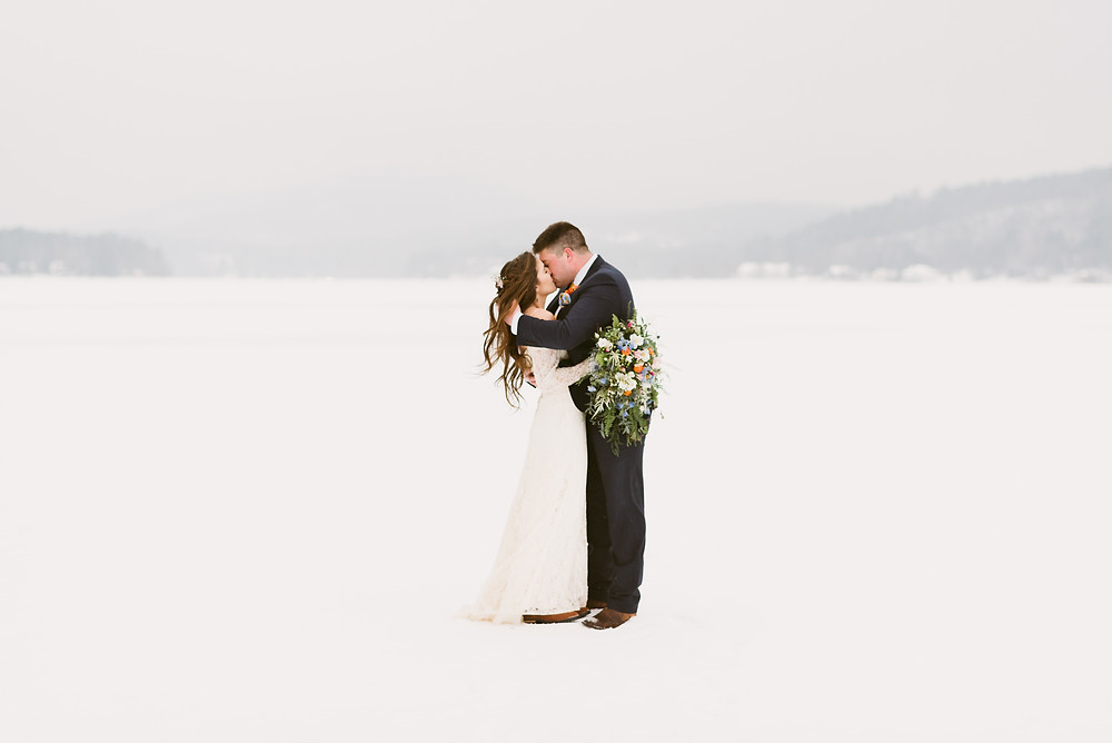 Bride and groom share a kiss at their winter wedding on frozen Schroon Lake in upstate New York