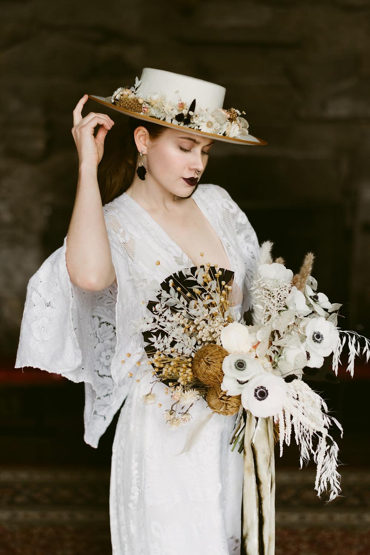 Bride wears dark lipstick and bolero hat for her wedding day