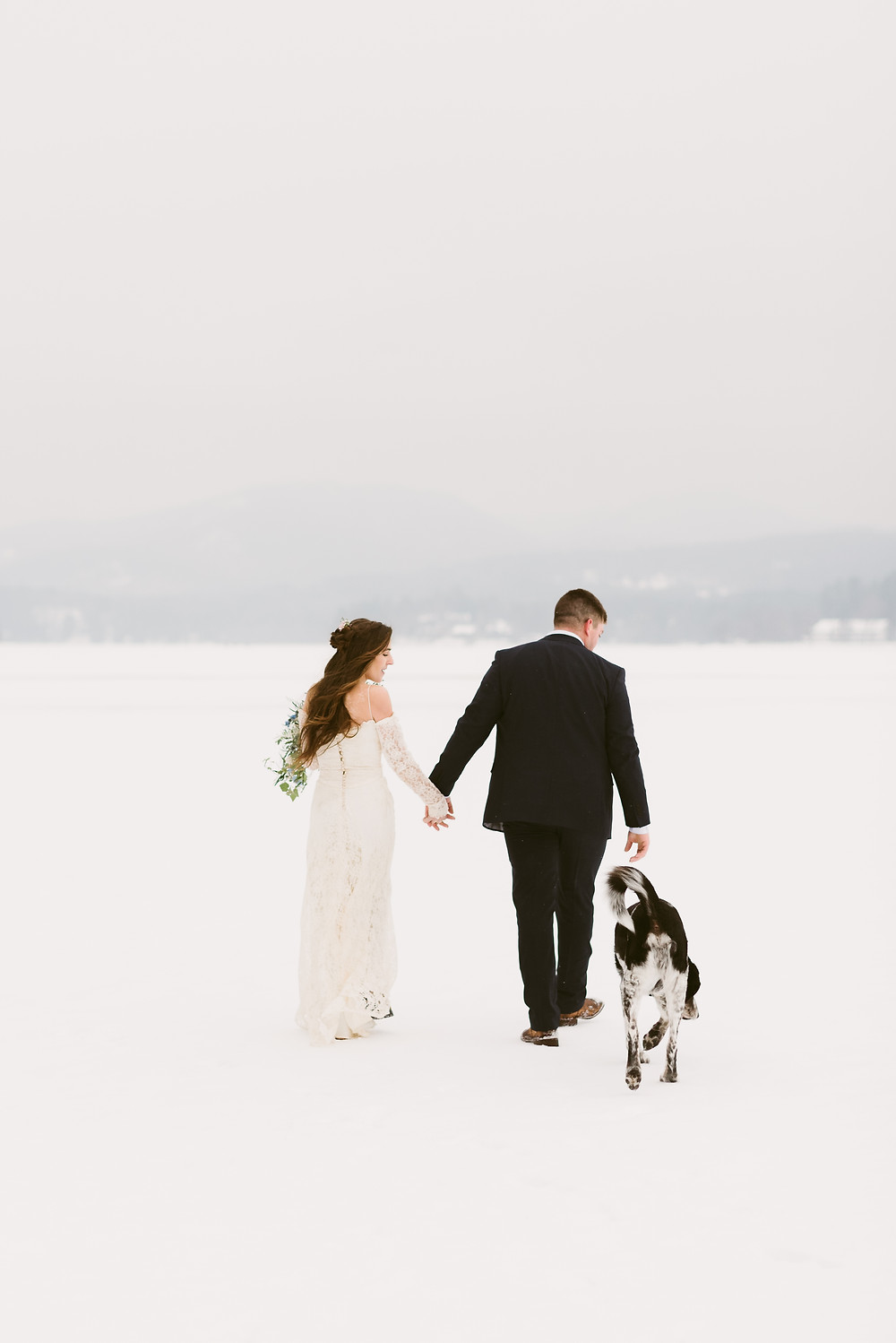 Bride and groom walk with their dog on frozen Schroon Lake