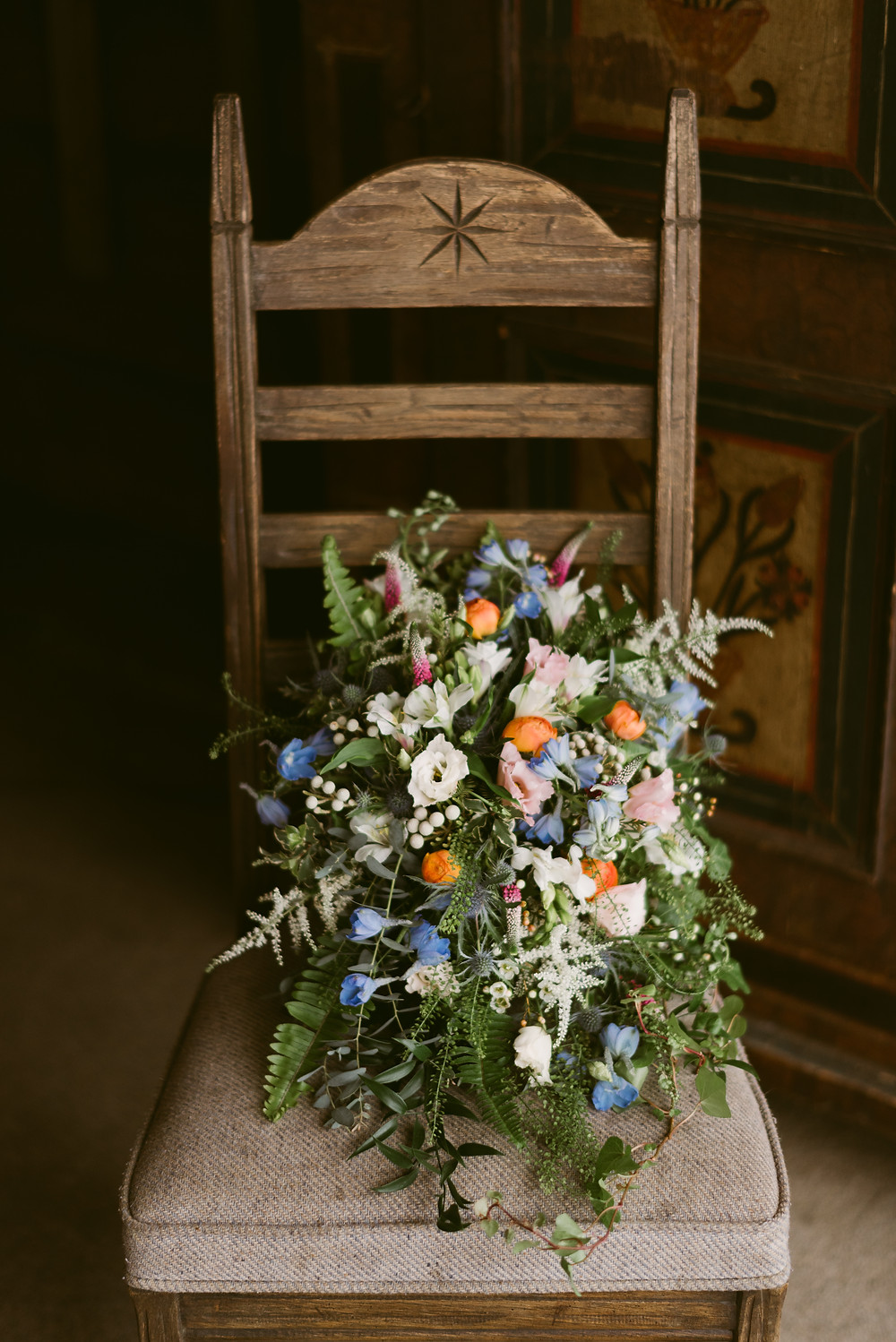 Beautiful bridal bouquet resting on antique wooden chair