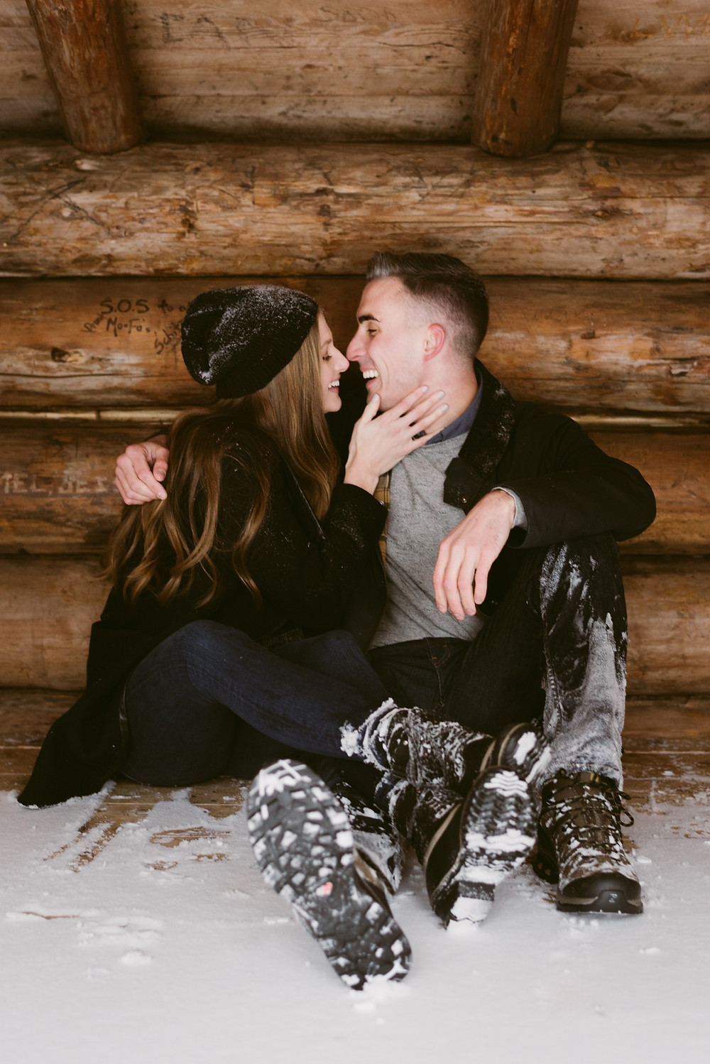 Snowy engagement session in a lean-to