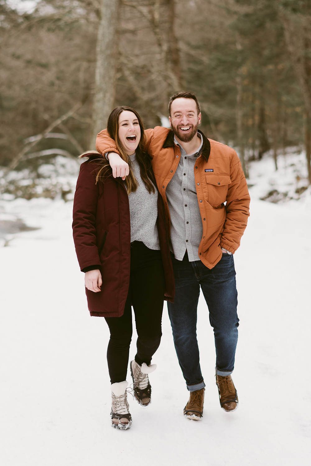 Laughing couple walking through snowy woods in upstate New York