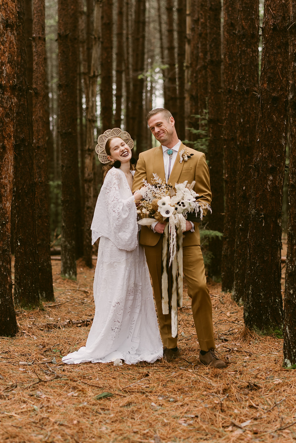 Couple stands amongst pine trees at The River Ranch for their wedding day in Lake Placid
