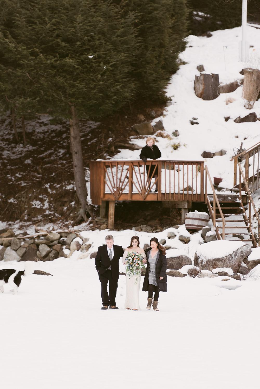 Parents escort bride onto frozen Schroon Lake for her winter wedding in upstate New York