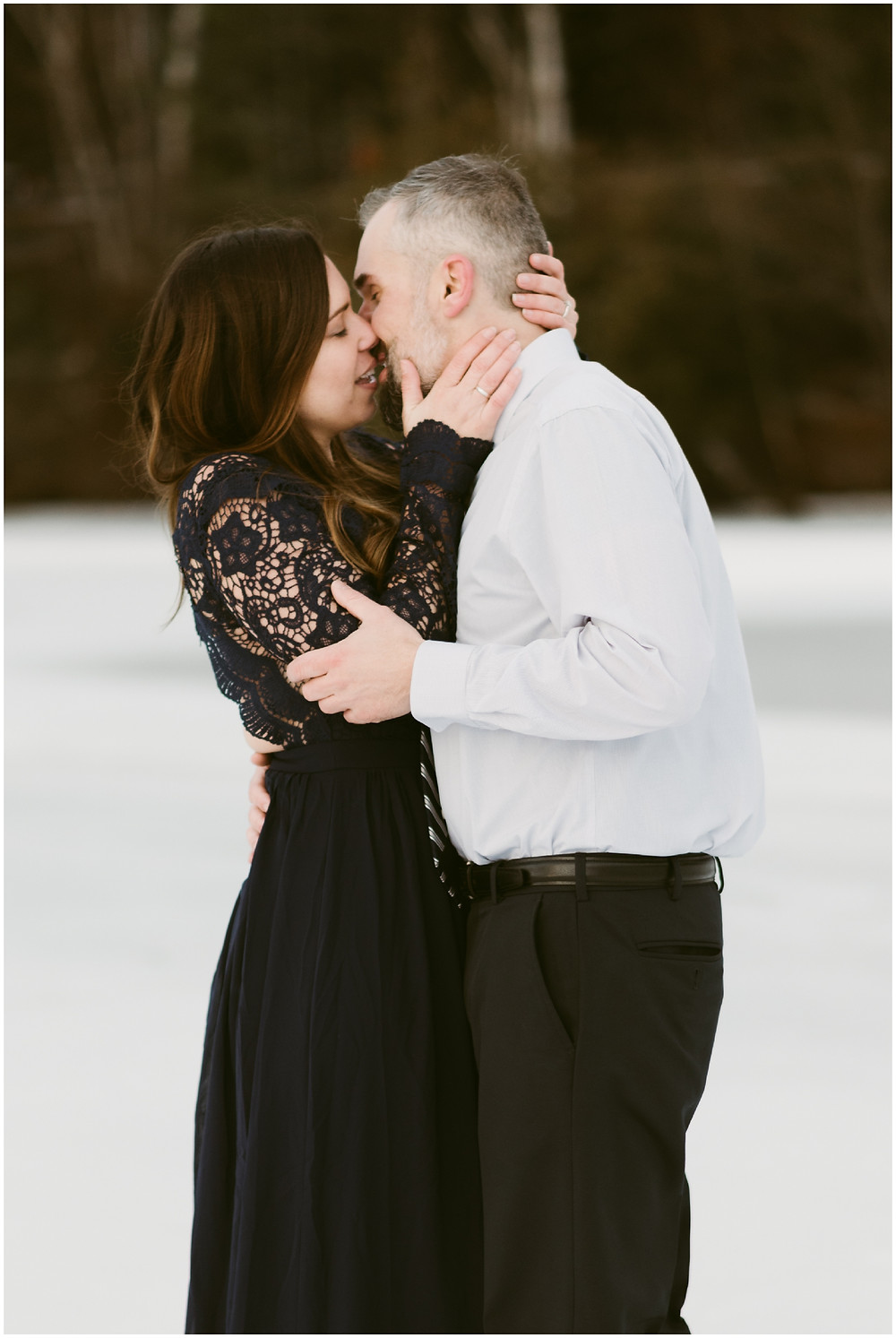 Engagement photo of couple standing on frozen Mirror Lake in Lake Placid, NY by Mountainaire Gatherings